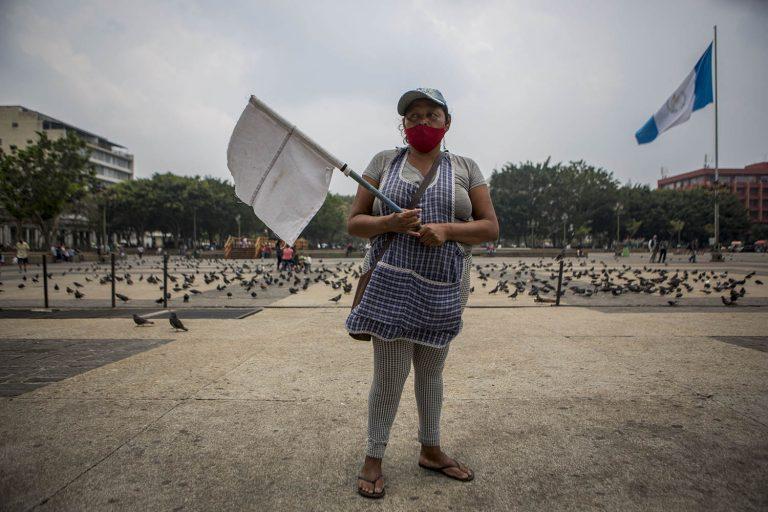Una mujer sostiene una bandera blanca como símbolo de que necesita ayuda o alimentos, en el parque central de Ciudad de Guatemala, el 13 de mayo de 2020. Foto\Oliver de Ros