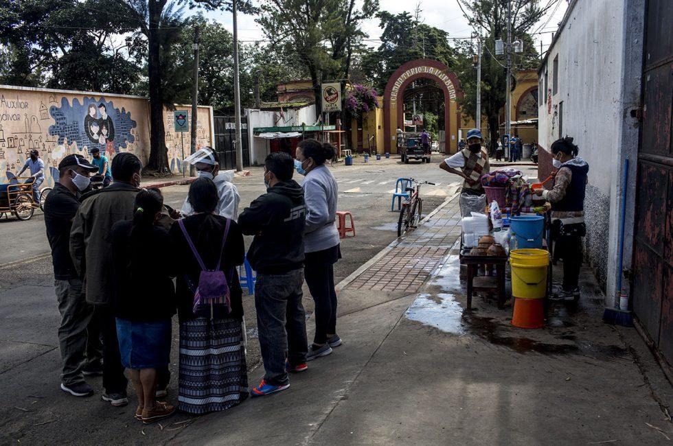 Familia de un fallecido por COVID-19 recibe disposiciones por parte del empleado de la funeraria contratada, en frente al cementerio de La Verbena. Foto: Plaza Pública/Simone Dalmasso.